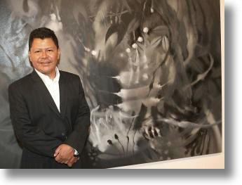 CARLOS JACANAMIJOY IN FRONT OF HIS MONOCHROMATIC PAINTING